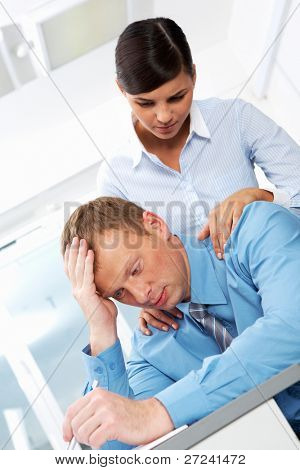 Portrait of business leader in trouble with young employee reassuring him