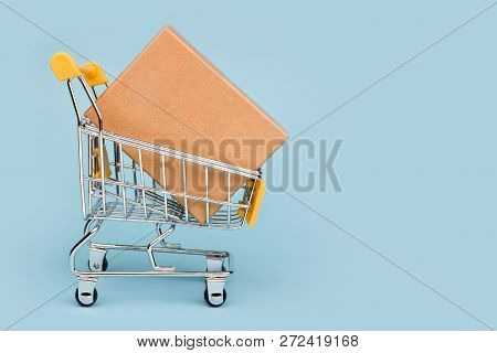 Miniature Shopping Cart With Large Box Isolated On Blue Background
