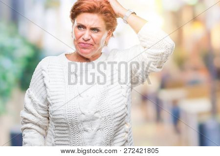 Atrractive senior caucasian redhead woman wearing winter sweater over isolated background confuse and wonder about question. Uncertain with doubt, thinking with hand on head. Pensive concept.