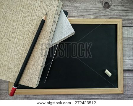 Concept Of Education With Stack Of Book And Pencil On Blackboard