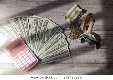 Us Dollar With Piggy Bank And Calculator On Wooden Background With Stripes Of Shadow With Soft Light