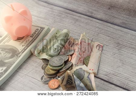 Financial Concept With Stack Of Us Money, International Currency And A Piggy Bank.