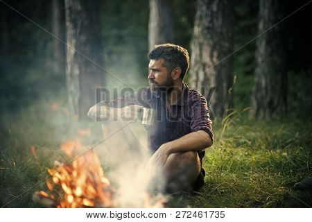 Hipster Hiker With Mug Relax At Bonfire In Forest. Camping, Hiking, Lifestyle. Man Traveler Drink Te