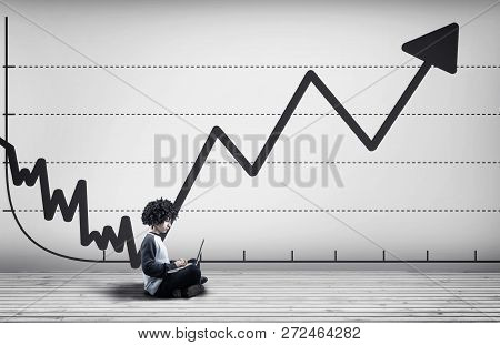 Young Man Working On Laptop In A White Room . White Wall Drawn With A Decreasing Graph And A Fast Op