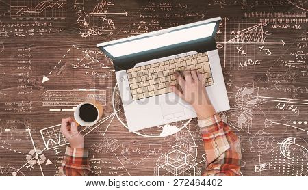 Top View Of Hands Holding A Cup Of Coffee And Using A Laptop On A Wooden Table Drawn With Math Formu