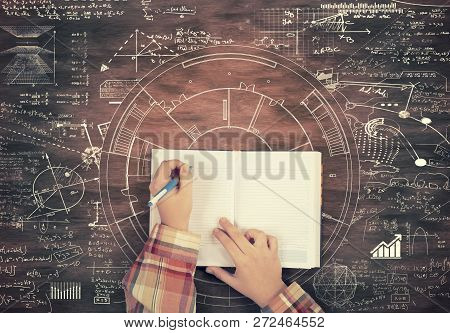 Top View Of Hands Writing On A Notebook Surrounded By Math Formulas And Sketches Drawn On Wooden Tab