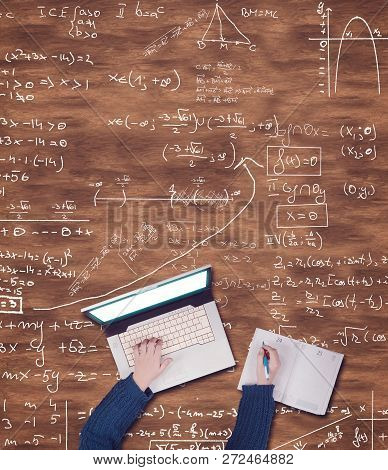 Top View Of Hands Using Laptop And Writing On A Notebook On A Wooden Table Drawn With Math Formulas.