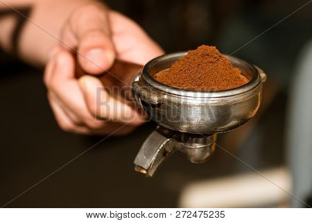 Making The Perfect Cup. Barista Hold Portafilter In Hand. Barista Brews Espresso Coffee In Cafe. Cof