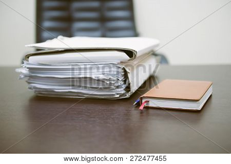 Notepad With Ballpoint Pen. Pile Of Unfinished Documents On Office Desk, Stack Of Business Paper. A