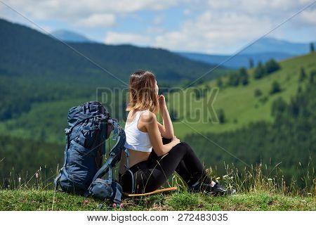 Young Female Backpacker With Blue Backpack Sitting On The Top Of A Hill, Looking Away, Enjoying Sunn