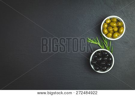 Set Of Green And Black Olives On Plate And Rosemary On A Black Stone Background. Free Space For Text