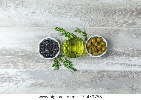 Set Of Black And Green Olives On Plates, Olive Oil And Rosemary On A Light Gray Wooden Background. T