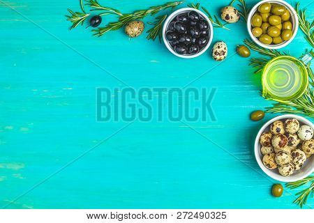 Set Of Black And Green Olives, Quail Eggs On Plates, Olive Oil And Rosemary, On A Blue Turquoise Woo