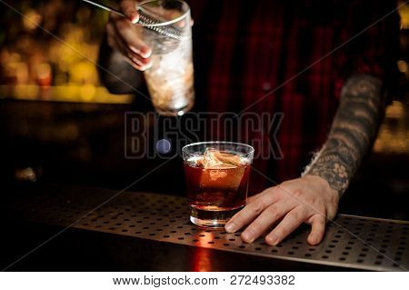 Bartender Holding A Godfather Cocktail And A Measuring Cup With The Strainer On The Bar Counter On T