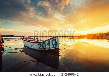Happy New Year 2019 Concept, Lettering On The Boat With A Reflection In The Water At Sunset