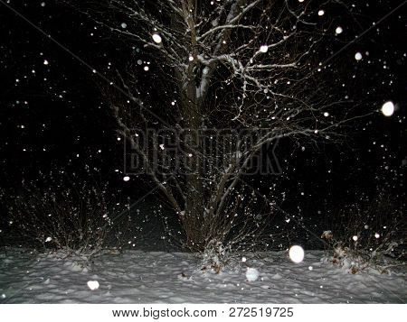 Abstract Featuring Snow Falling Against The Night Sky.