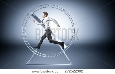 young businessman run in huge hamster wheele