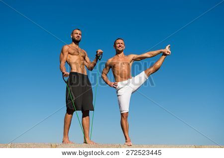 Muscular Men Training On Fresh Air. Reach Balance By Virtue Of Yoga. Sport And Health Care. Daily Ex