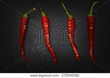 Red dry chilli peppers on black background