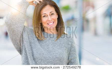 Beautiful middle age woman wearing winter sweater over isolated background confuse and wonder about question. Uncertain with doubt, thinking with hand on head. Pensive concept.