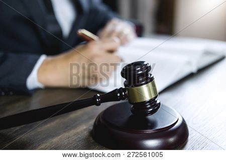 Counselor Or Male Lawyer Working On Courtroom Sitting At The Table. Legal Law, Judge Gavel With Just