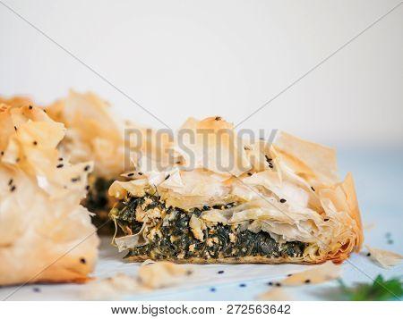 Greek Pie Spanakopita On Blue Table With Shallow Dof. Slice Of Vegetarian Or Vegan Spanakopita Spina