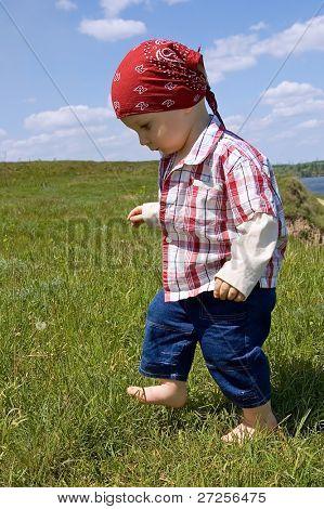 1,5 anos de idade, descalço, baby boy-o para sair-se vigorosamente contra a paisagem de Verão