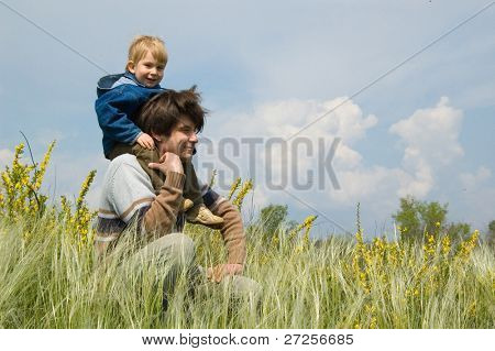 happy father and little son rest on the field of feather-grass