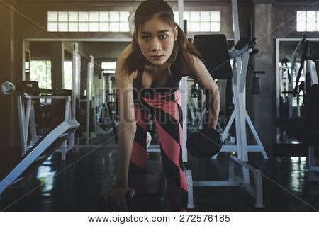 Young Woman With A Barbell, In A Beautiful Sports Uniform,her During An Exercise In A Gym.