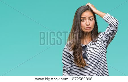 Young beautiful arab woman wearing sunglasses over isolated background confuse and wonder about question. Uncertain with doubt, thinking with hand on head. Pensive concept.