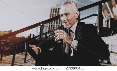 Businessman Is Using A Tablet Pc. Businessman Is Old Smiles Man. Businessman Is Holding A Coffee Cup