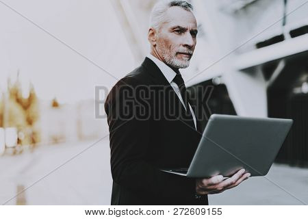 Businessman Is Holding A Laptop Computer. Businessman Is Old Serious Man. Man Wearing In Black Suit.