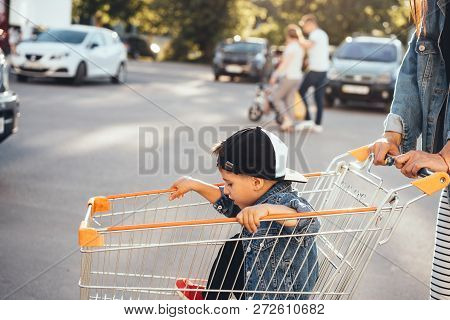 Small Boy, Mom Carries In A Cart Near The Supermarket.