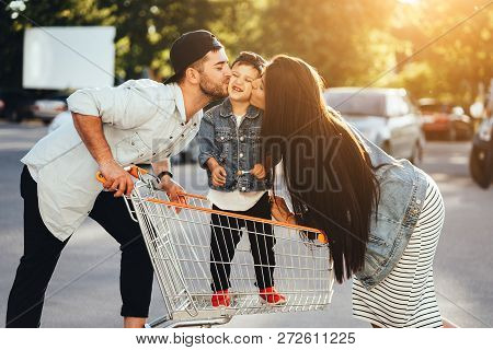 Young Parents Put Their Son In A Cart And Kiss Him In The Parking.