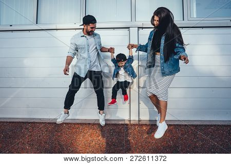 Young Family Is Having Fun On The Street Near The Wall