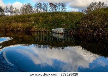 View On Autumn Landscape Of River And Boat In Sunny Day. Forest On River Coast In Autumn Day. Reflec