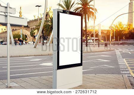 Mockup of a blank empty advertising urban billboard, placeholder template on city street, space for design layout, sunset light. poster