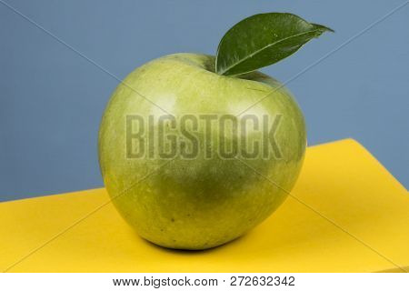Green Apple Fruit On Top Of A Book Stack, On The Back Of School Classes