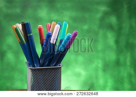 Creativity Of Colorful Colored Pen In Pencil Case With Copy Space On Blurred Green Background.