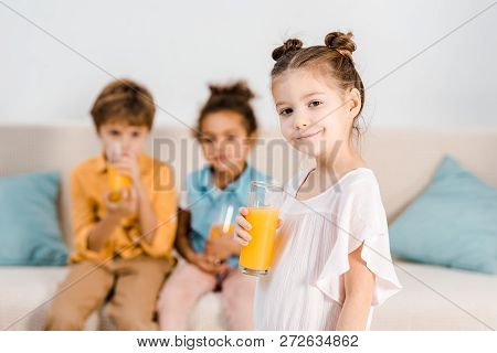 Adorable Child Holding Glass Of Juice And Smiling At Camera While Little Friends Drinking Juice Behi
