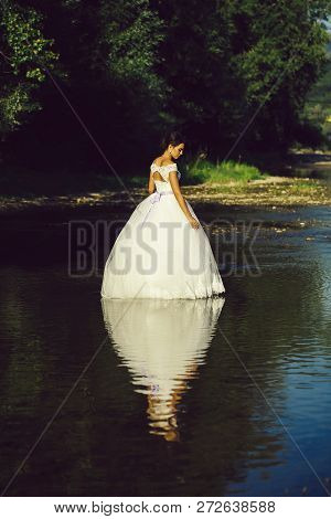 Pretty Bride Pretty Woman In Long Elegant White Lace Wedding Dress Stands In Lake Water Sunny Day Ou