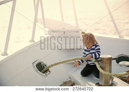 Travel And Summer Vacations. Baby Care And Childhood. Little Child Sitting And Berthing Rope On Whit