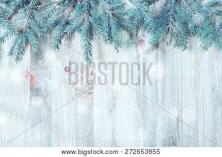 Winter Christmas and New year background. Blue fir tree branches with winter snowflakes on the wooden background. Winter still life, free space for festive Christmas and New year text