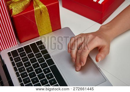 Cropped View Of Woman Using Touchpad On Laptop Near Wrapped Presents