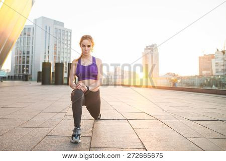 Portrait Of A Young Sports Girl Squatting Against The Background Of The Sunset. Girl In Sports Wear