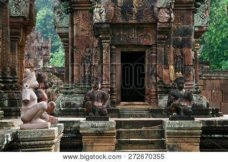 Doorway On An Ancient Lichen Covered Jungle Ruin In Asia With Guardian Statues Sitting Outside For P