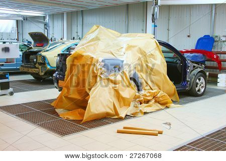 The image of cars stand under repair in body shop
