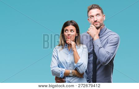 Young workers business couple over isolated background with hand on chin thinking about question, pensive expression. Smiling with thoughtful face. Doubt concept.