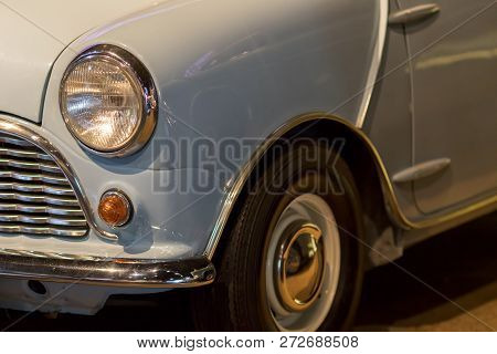 Vintage Car. Classic 1960s British Car In Close-up. Headlight And Front Wing Of A Pale Blue Small Au