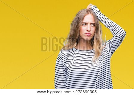 Beautiful young blonde woman wearing stripes sweater over isolated background confuse and wonder about question. Uncertain with doubt, thinking with hand on head. Pensive concept.